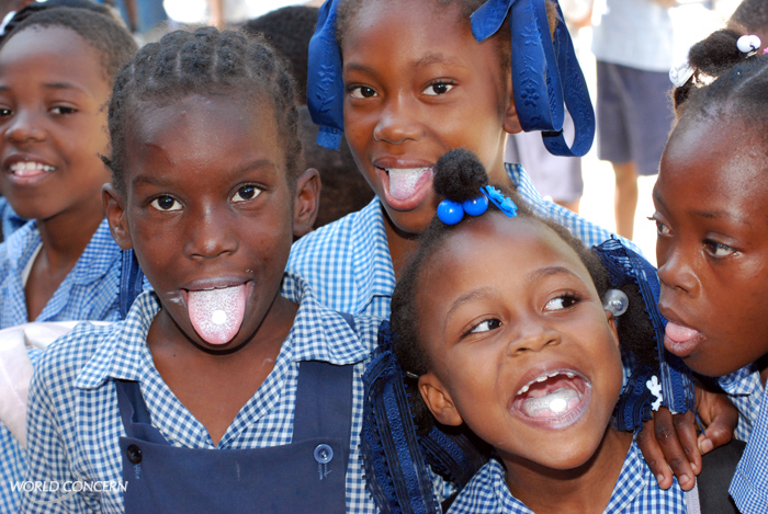 Happiness in Haiti! The deworming medication easily dissolves on the tongue.