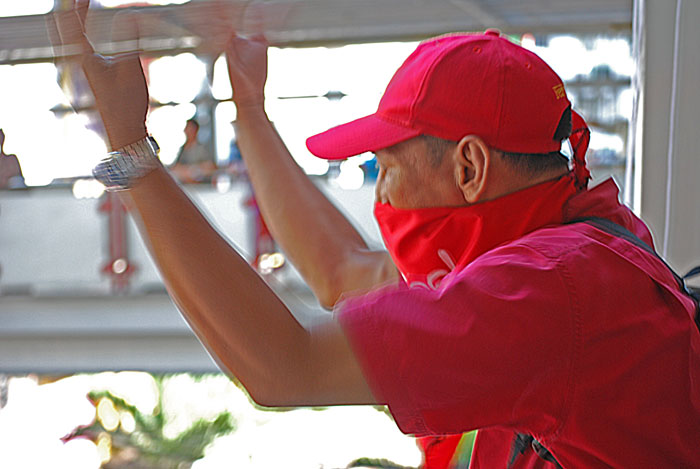 """A """"red shirt"""" anti-government protester motions to his friends to join him inside a Bangkok rail station."""