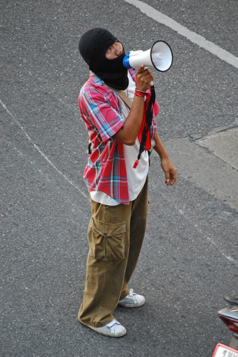 """A """"red shirt"""" protester wearing a mask uses a megaphone to help coordinate outside Bankok's Siam Pavilion mall."""