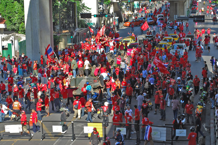"""Hundreds of anti-government """"red shirt"""" protesters climb on top of two tanks in Bangkok April 12."""