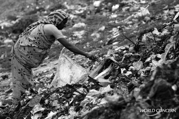 A woman picks through rotting trash in a slum in Dhaka, Bangladesh.