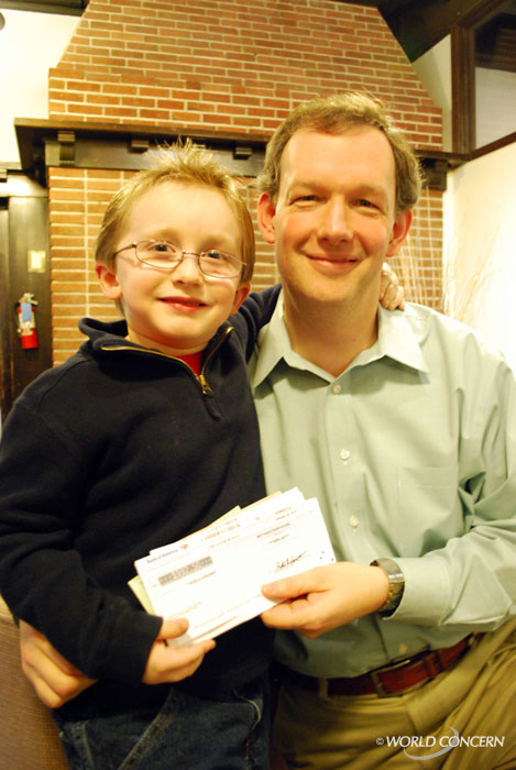 Six-year-old Jonathon Kane gives World Concern President Dave Eller a handful of checks after a week and a half of Haiti fundraising.