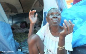 A Haitian grandmother outside her tent.