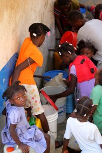 Girls filling buckets of water.