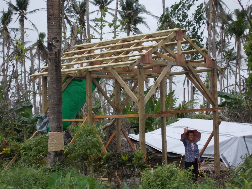 Rosario waves from inside the frame of her new home. Her former home was destroyed when Typhoon Haiyan ripped through the Philippines. Photo courtesy of Medair.