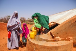 Women draw water from a berkad.