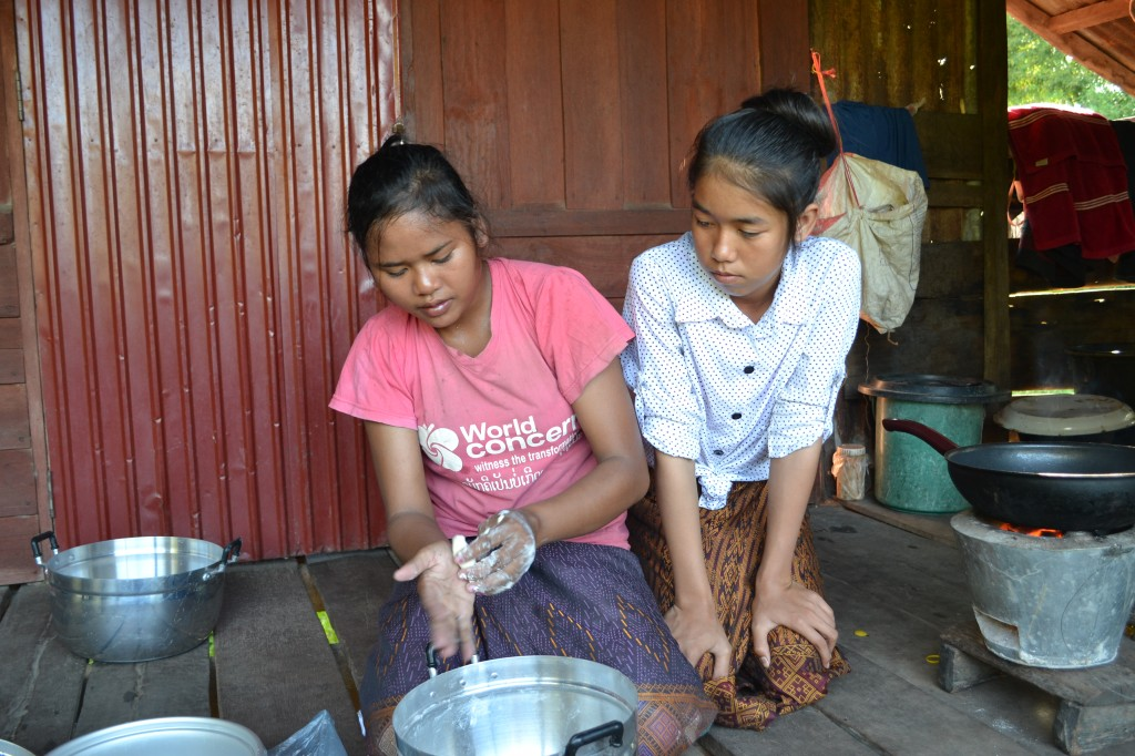 Leh teaching her friend how to make sticky sticks, so she can earn income too.