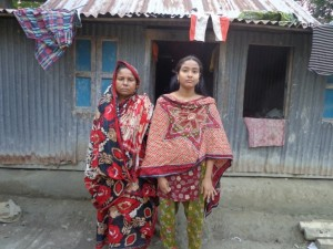 Karima (right) stands with her mom outside their home.