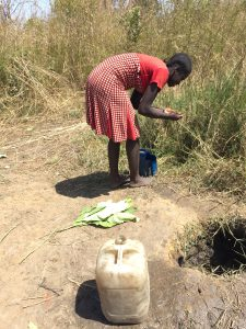 14-year-old Mary waits for a hole in the ground to fill with muddy water so she can fill her water can.