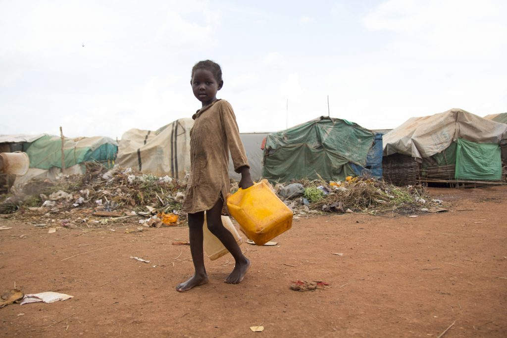 a girl collects water in an IDP camp in South Sudan