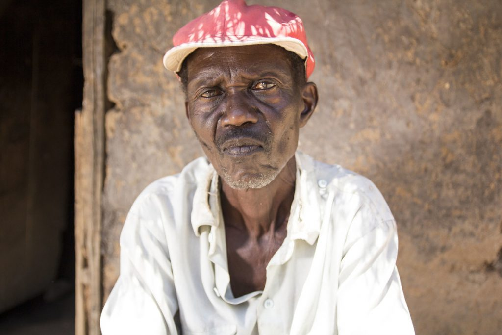 a man sits outside his home in Uganda