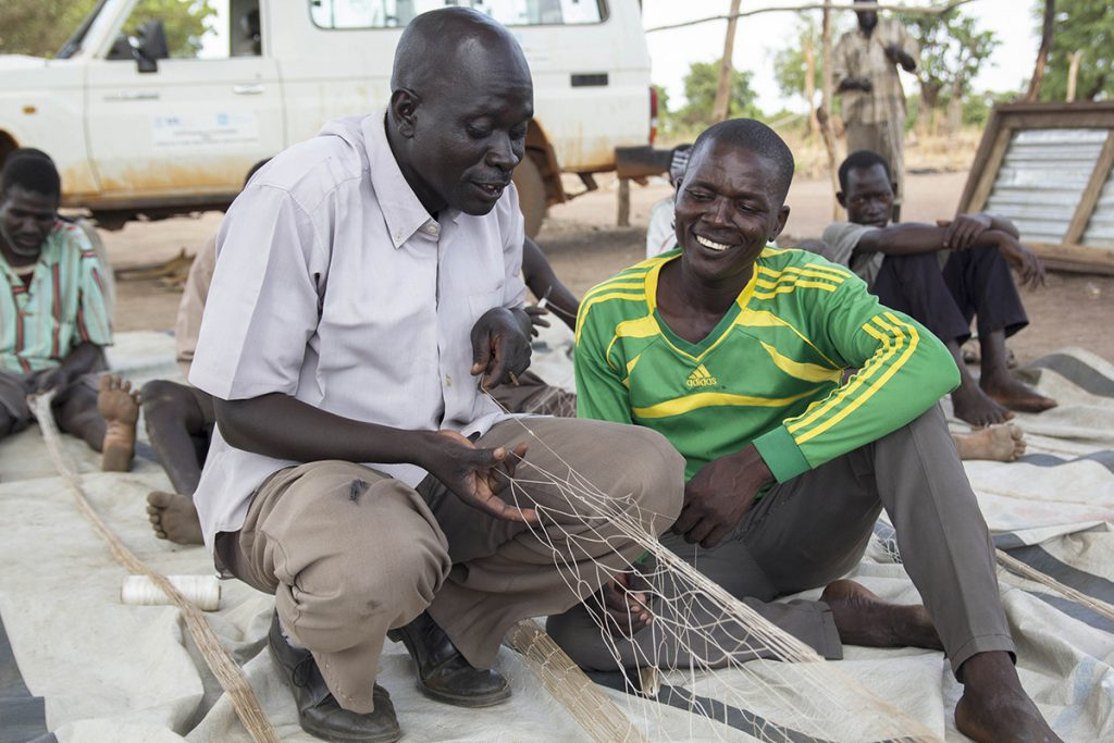 a man learns how to fish and make nets in South Sudan
