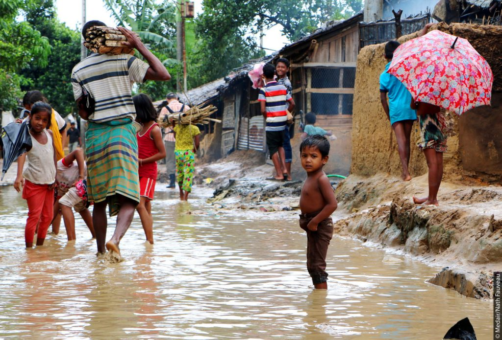 A boy wades through water in a refugee camp in Bangladesh