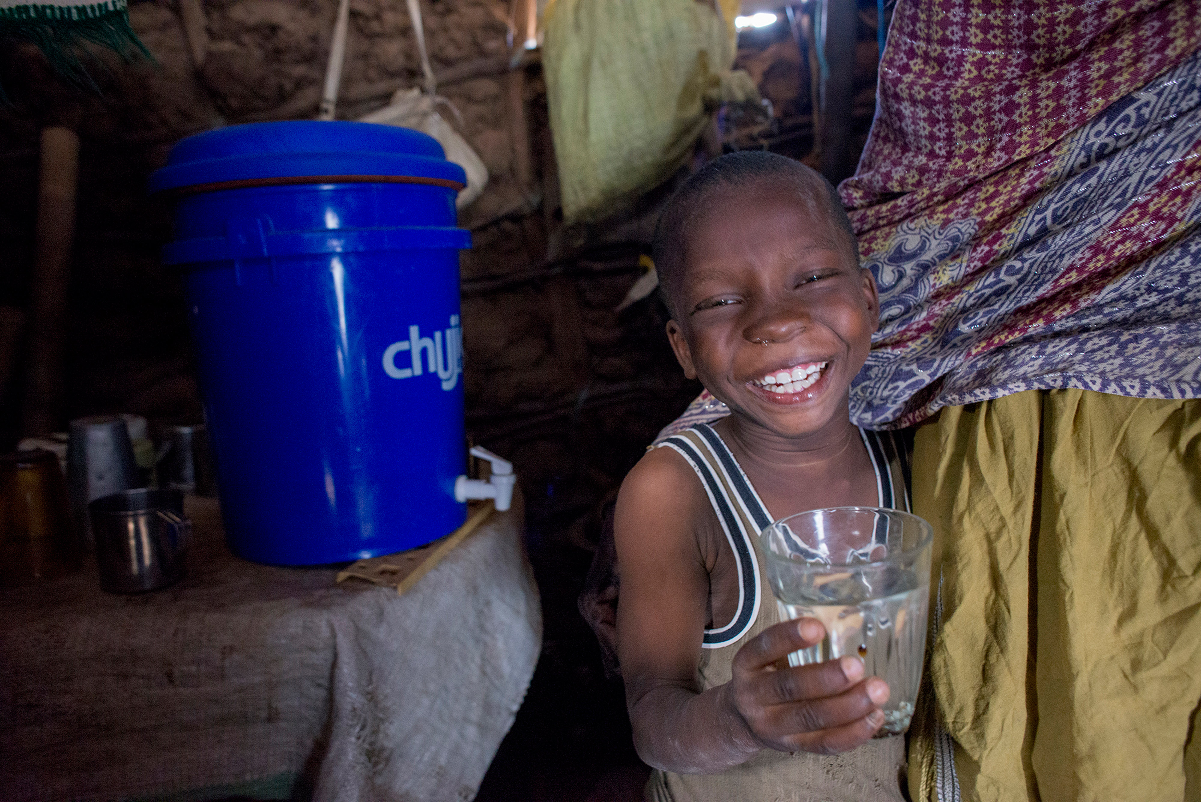a boy smiles holding a water glass